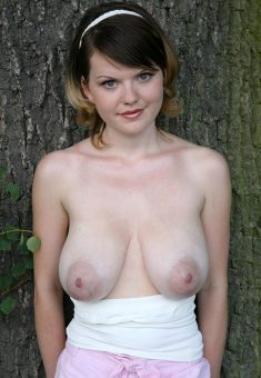 Young girl with pretty face shows her big natural boobs
