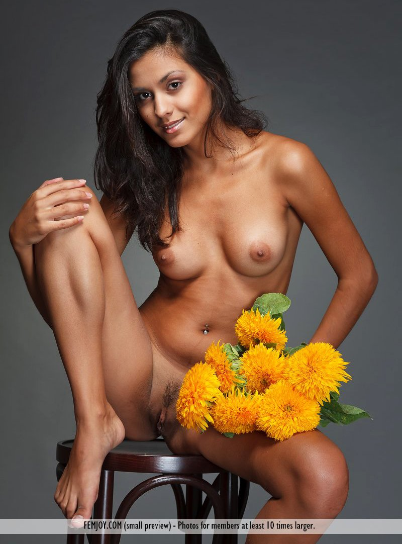 Brunette Adrienne puts down a bunch of flowers while modeling in the nude