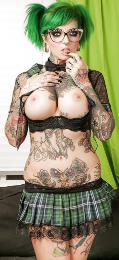 Tattooed girl in glasses Sydnee Vicious showing off tattoos in pleated skirt