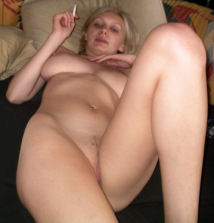 Horny blonde with Big Boobs smokes naked on the bed